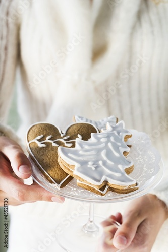 Hands holding glass bowl of assorted gingerbread biscuits