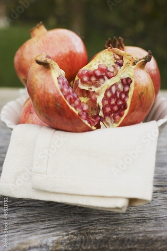 Pomegranates, whole and halved, on cloth in white bowl