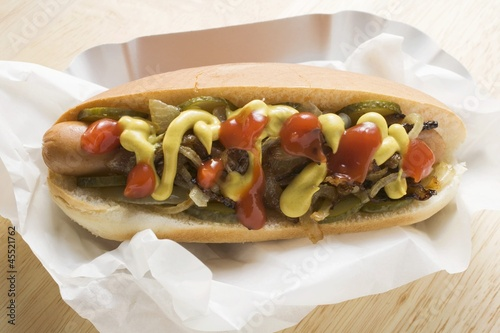 Hot dog with mustard, ketchup, gherkins and onions