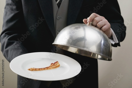 Butler serving rasher of fried bacon on plate with dome cover