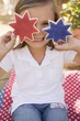 Small girl holding two star cookies (4th of July, USA)