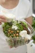 Woman pouring dressing over salad in plastic container