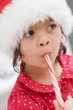 Small girl in Father Christmas hat eating candy cane