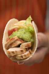 Hand holding a taco filled with chicken and guacamole