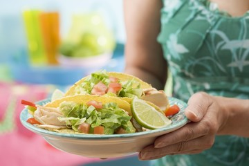 Woman holding plate with two chicken tacos