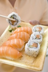 Woman holding sushi on plastic tray