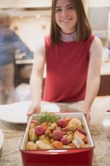 Young woman holding roasted root vegetables in roasting dish