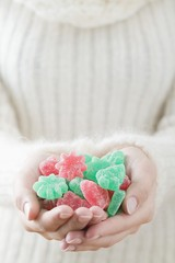 Woman holding sugar-coated jelly sweets (Christmas)