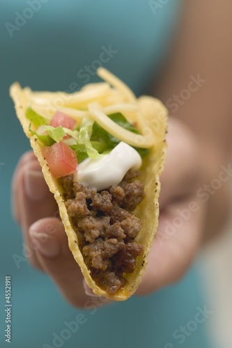 Hand holding taco filled with mince, cheese & sour cream
