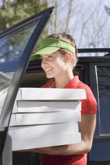 Smiling woman with several pizza boxes