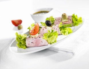 Rolls of ham filled with lettuce leaves