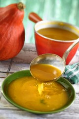 Pumpkin soup being poured into soup plates