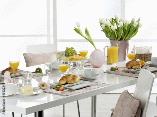 A table laid for breakfast with white tulips and croissants