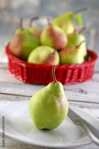 A pear on a plate in front of a basket of pears