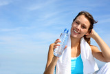 Thirsty fitness girl holding bottle of water