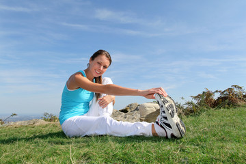 Young woman doing stretching exercises outside