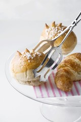 Milk rolls and croissant with cake tongs