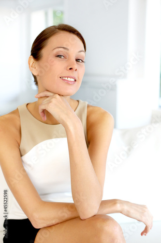 Portrait of attractive woman sitting in couch