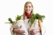 Blond chef holding two bags of vegetables