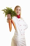 Blond female chef showing bunch of carrots