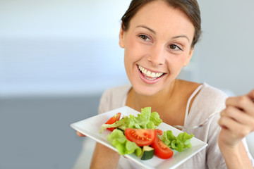 Closeup of cheerful woman eating fresh salad