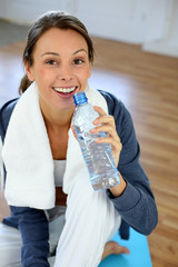 Girl sitting in gym with bottle of water