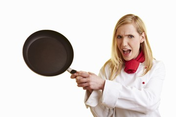 Blond female chef brandishing frying pan