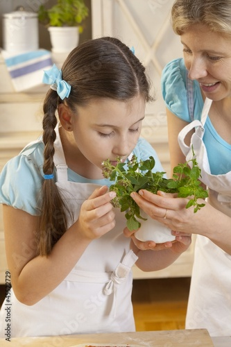 Mother and daughter with fresh herbs in kitchen