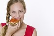 Young woman eating a slice of bread with strawberry and rhubarb jam