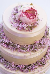 Three-tiered cream cake with spring flowers