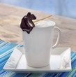 Steamed Milk in a White Mug with a Pear Shaped Chocolate Stick