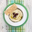 Hummus with Olive Oil and Olives in a Bowl with Sesame Seed Flat Bread