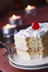Tres Leches Cake with Cinnamon and a Cherry; Partially Eaten