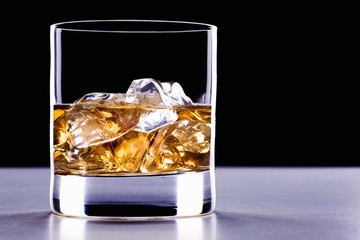 A glass of whisky with ice cubes