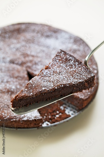 A chocolate cake with a piece on a cake slice
