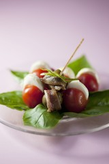 An appetiser consisting of sardines, olives, tomatoes and mozzarella