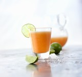 Glass of Cantaloupe Ague Fresca with Lime Garnish; Pitcher of Cantaloupe Agua Fresca