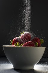 Sugar Pouring Over a Bowl of Strawberries