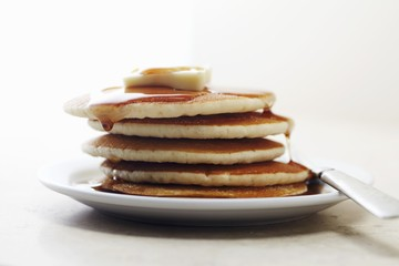Pile of pancakes with maple syrup and butter