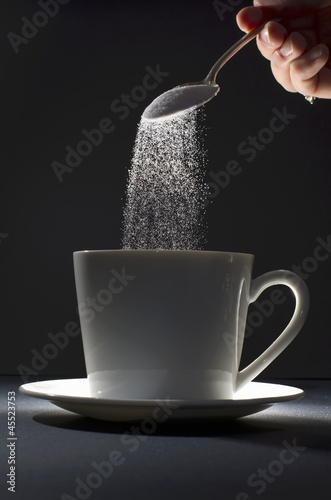 Pouring Spoonful of Sugar into a Coffee Mug
