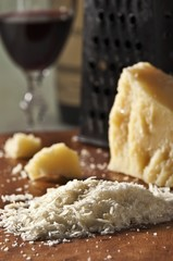 Grated Romano Cheese with Cheese Grater and Glass of Red Wine