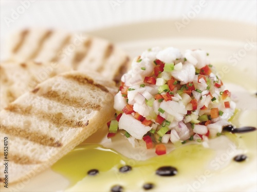 Citrus Ceviche of Bass Fish with Grilled Bread on a White Plate