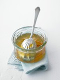 Orange marmalade in a glass dish with a spoon