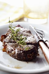 Steak with a Sprig of Oregano on a Plate with Fork and Knife