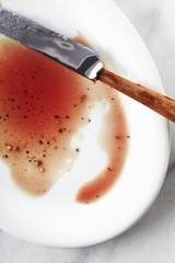Juices from a Cooked Steak on a White Plate; Knife