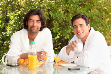 men dressed in bathrobe drinking coffee at breakfast