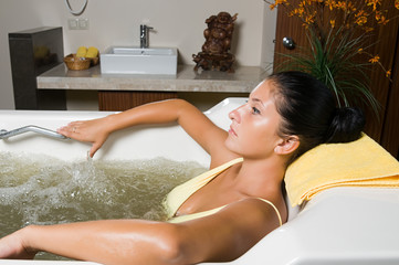 Beautiful young woman relaxing in jacuzzi filled with seawater