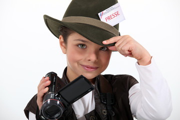 little girl taking a camera and wearing a costume of journalist