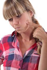 Blond woman touching her cheek