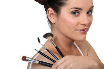 cute brunette with make-up brushes